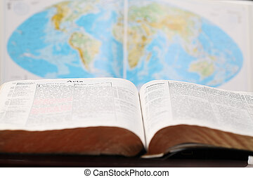 World Missions - Bible open to the Book of Acts and a world...
