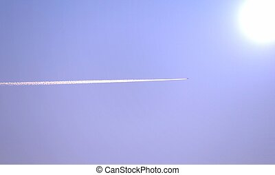airplane with white smoke trail flying towards the sun -...