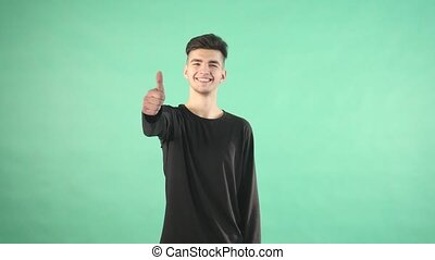 young man smiling with thumbs up isolated on a green background