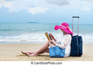 girl tourist sits on the beach hold her ipad