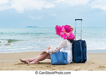 girl tourist sits on the beach with luggage bag