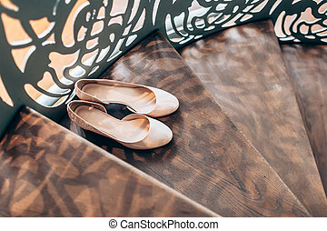 Peach women's wedding shoes on wooden stairs with derative...