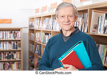 Mature Male Student Studying In Library