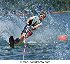 Young Slalom Skier - A young boy going around a bouy on a...