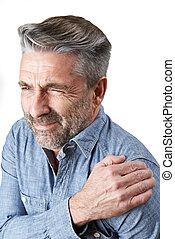 Studio Shot Of Man Suffering With Frozen Shoulder