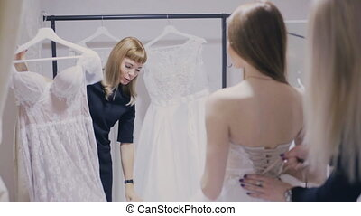 Consultant shows wedding dress in bridal shop - girl and...