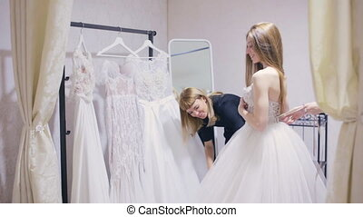 Pretty woman chooses a wedding dress in bridal shop - Young...