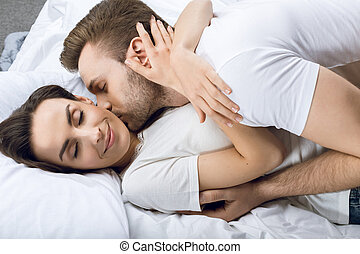 man kissing smiling woman in bed