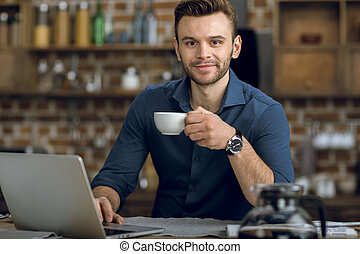 young man with coffee cup using laptop and smiling at camera...
