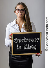 Customer is King - Young businesswoman holding chalkboard...