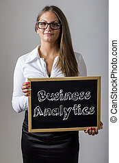 Business Analytics - Young businesswoman holding chalkboard...