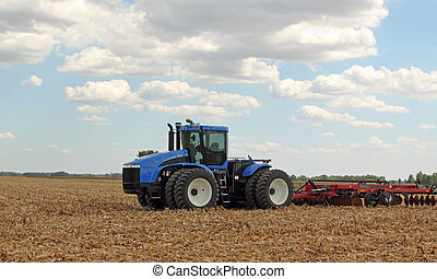 Tractor and Plow - Farm tractor pulling a plow in a...
