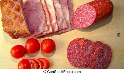 ham, salami, and tomatoes are on the Board.