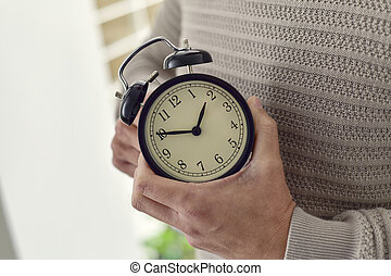 man winding or adjusting the time of a clock - closeup of...