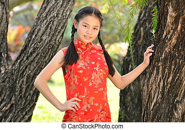 12 years old Asian girl in red Chinese new year Dress post...