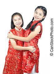 12 years old Asian girls hug in red Chinese new year Dress,...