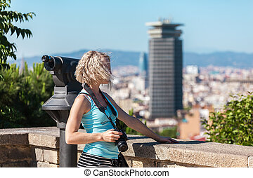 Female traveler standing with camera against the background...