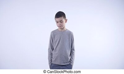 Sad brunette kid over isolated white background.