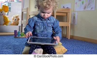 Adorable child using tablet computer in his room. Handheld...