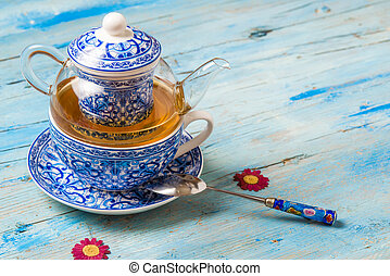 Teapot, teacup and spoon on blue wooden table