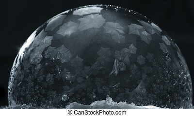 Frozen bubble with flying snowflakes, winter holidays...