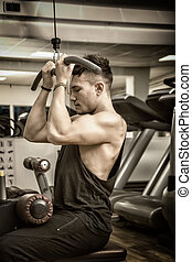 Young man training on gym equipment, pulling handle on...