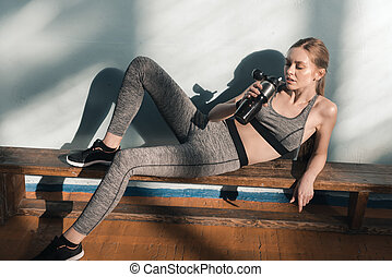 woman on bench drinking water from sports bottle - sporty...
