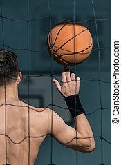 man holding basketball ball on finger