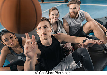 young people looking at man balancing ball on finger