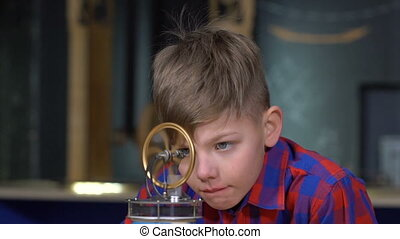 The boy and the Stirling engine - The boy looks at the...