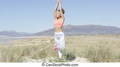 Woman doing yoga on the beach - Attractive young woman...