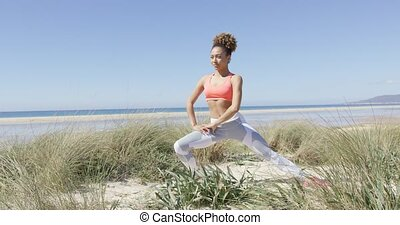 Woman warmin up on the beach - Young sporty woman stretching...