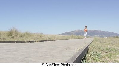 Woman running on a pavement - Young pretty woman training...