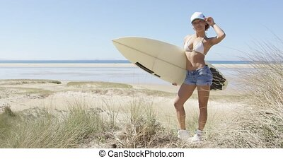 Young woman standing with the surf - Attractive woman on the...