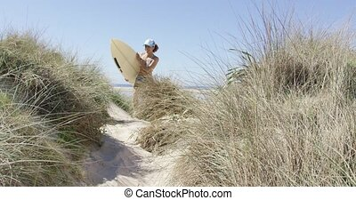 Woman running with the surfboard - Young woman running on...