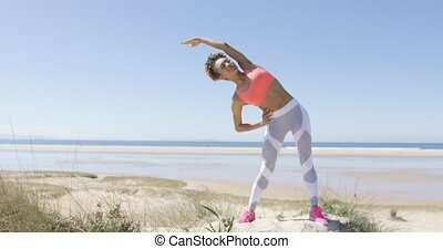 Woman stretching by the sea - Young sporty female doing the...