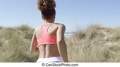 Woman jogging on beach - Back view of sporty woman doing...