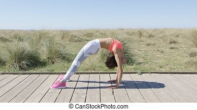 Woman in bridge position - Side view of young woman standing...