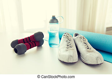 close up of bottle, dumbbells, sneakers and mat
