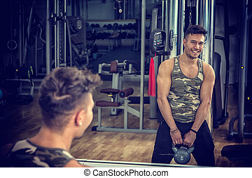 Young man working out in gym with kettlebells
