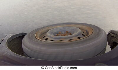 Rolling rubber tire of dark blue car on the asphalt road.