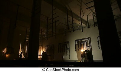 Silhouettes of workers lit by welding flashes at the dark...