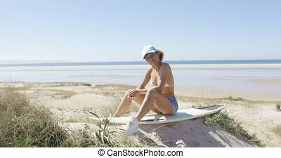 Woman sitting on a board - Young woman wearing cap sitting...