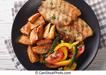 White fish fillet and potato wedges, fresh salad close-up....