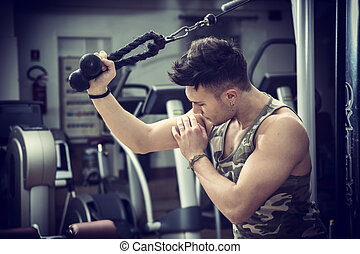 Young man training on gym equipment