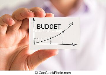 Businessman holding a card with BUDGET rising arrow and chart