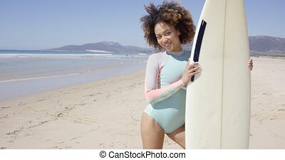 Smiling female standing with surfboard - Smiling female...
