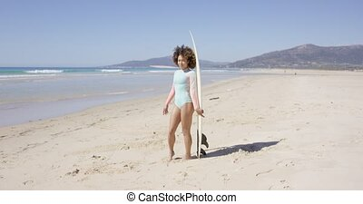 Female posing on beach with surfboard - Young female wearing...