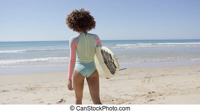 Female walking into sea to surf - Female holding surfboard...