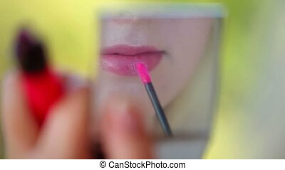 Young woman doing makeup with lipstick looking to handheld...